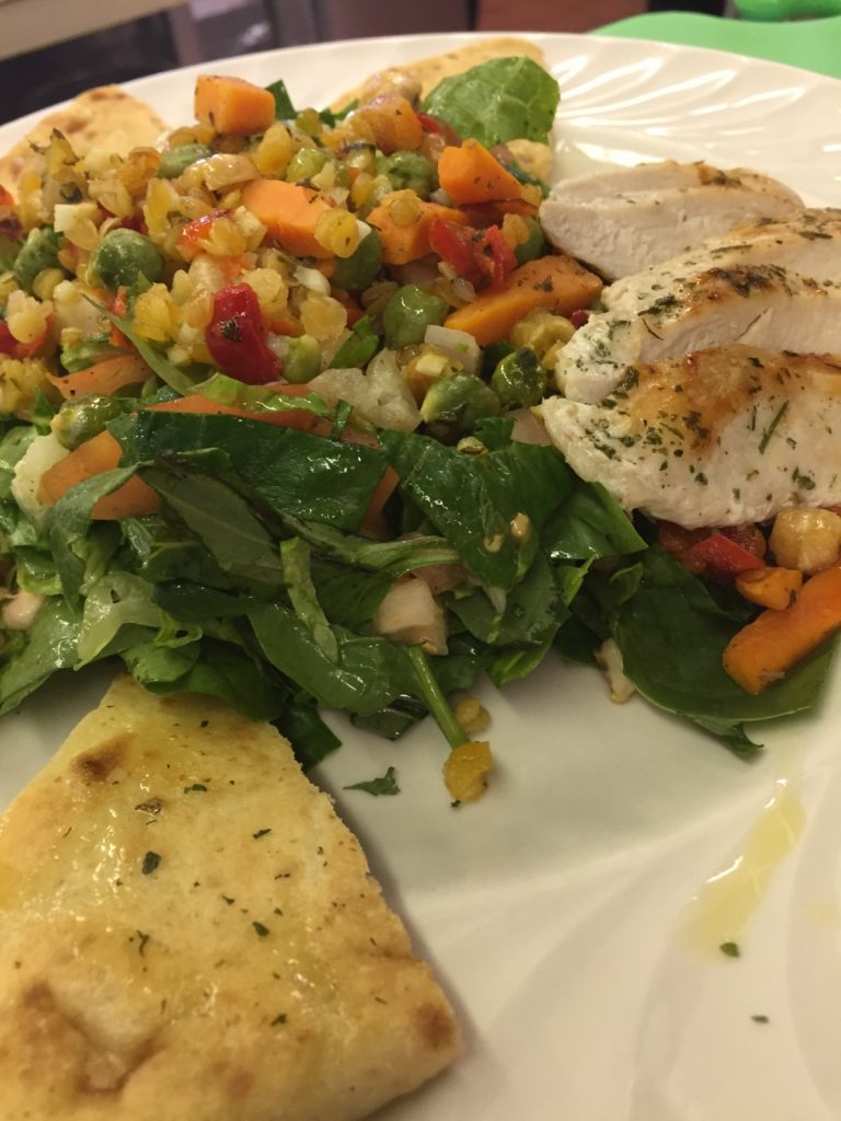 Protein Salad made of perfectly grilled chicken breast, a colorful blend of cooked garbanzo beans, carrots, red bell pepper, cooked red lentils, house seasoning over mixed greens